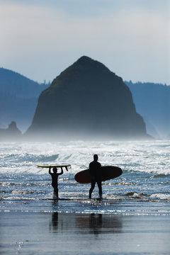 A father and son surf along the Oregon Coast.
