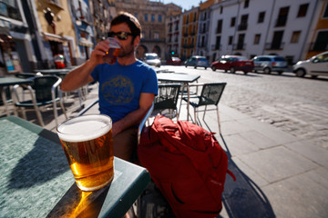 A man has a beer in the main square in the old town section of Cuenca, Spain, a UNESCO World Heritage Site..