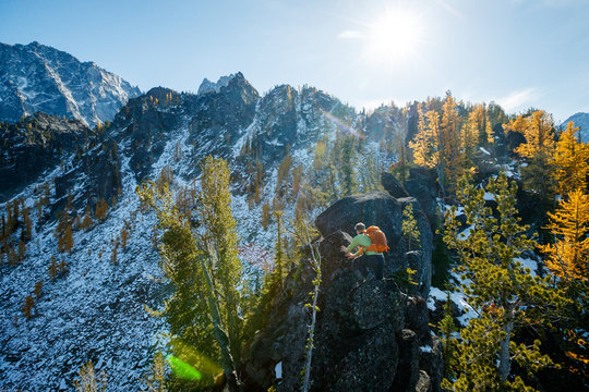 A man with a pack traverses an exposed rocky ridge amidst fall colors near Colchuck Lake in the Cascade Range of Washington State.