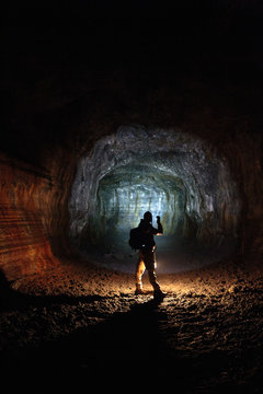 A male caver holding a propane lantern and flashlight while exploring the 13,042 foot long Ape Cave near Mount St. Helens in the Gifford Pinchot National Forest of western Washington State. The cave is the third longest known lava tube in North America. The cave is open year round and has a easier, shorter lower cave section and a slightly more physical and longer upper cave section.