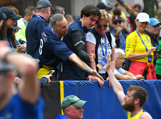 Bill Richard, father of Boston Marathon bombing victim Martin Richard, left, congratulates a man  running for the Martin Richard Foundation, after he completed the 123rd Boston Marathon in Boston