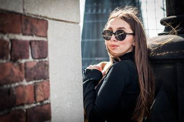 Young beautiful woman with long brown hair in sunglasses on a walk on a cloudy day. Fashionable sexy girl. Street fashion look. Cute student