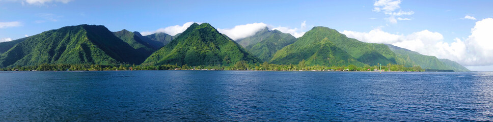 DRONE Flying over the deep blue sea and towards the towering mountains of Tahiti