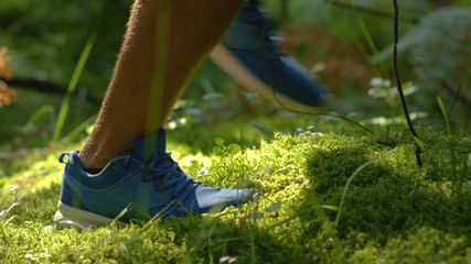 CLOSE UP, DOF: Fit man jogging through the forest and along the mossy ground.