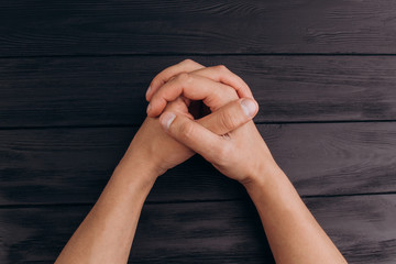 interlocked fingers, white male hands interlocked on black rustic wood table close up. top view. a man is waiting for negotiations