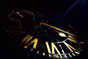 Clock face with golden spades shape hour hand and roman numerals
