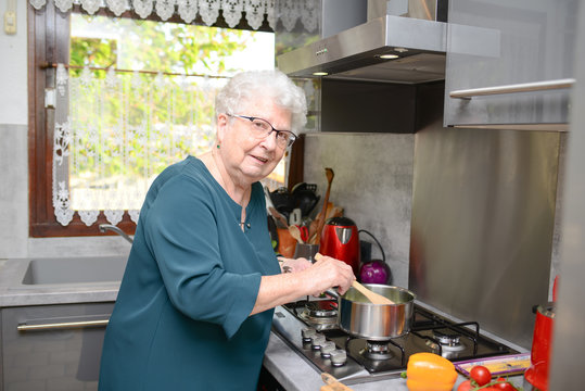 happy senior active woman cooking at home in a modern kitchen