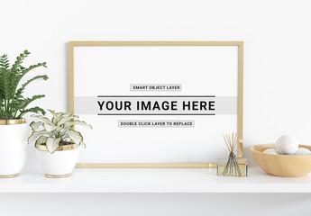 Horizontal Frame Leaning on Shelf With Plants Mockup