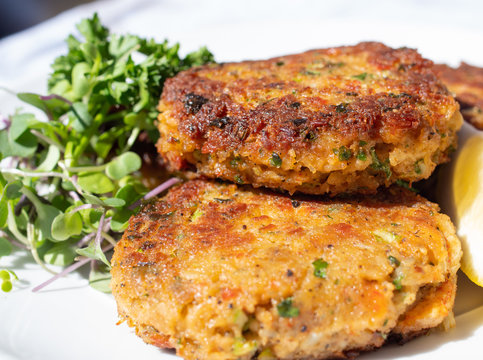 Savoury, crisp and starchy, fishcakes, crab cakes..Fried fish patties served on a plate with salad on the side.