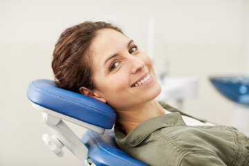 Portrait of smiling young woman lying in dental chair and looking at camera, copy space