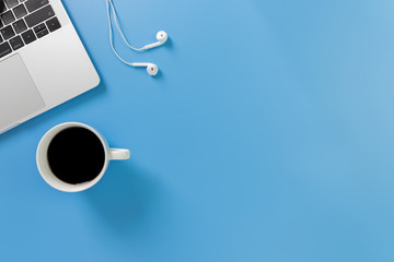 Wall Mural - Listening to music at work. Flat lay desk top with laptop, earphone, coffee on blue background. Cool tone.