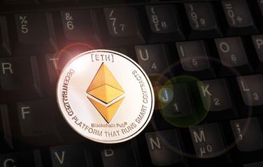 Golden Ethereum ETH coin over black keyboard