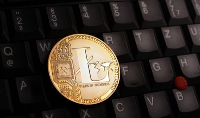 Golden litecoin LTC coin over laptop keyboard