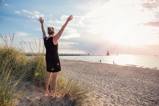Woman with her arms raised on a dune at the beach