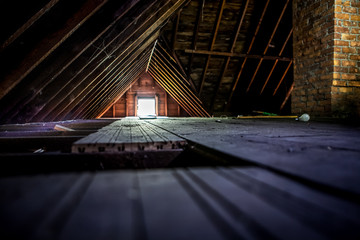Old attic space with roof rafters and a window