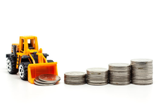 A yellow toy bulldozer with pile of coins on white background for saving money, investment, business and finance concept