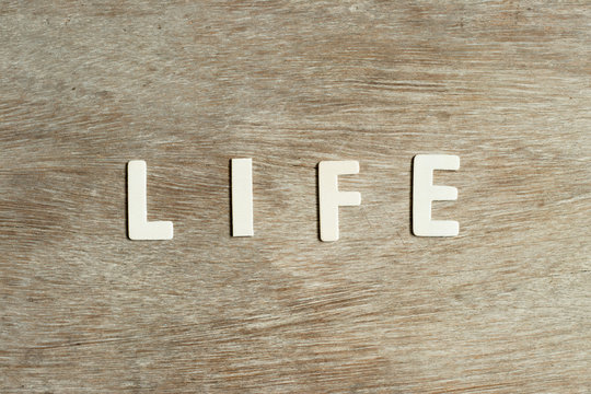 Alphabet letter in word life on wood background