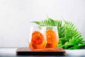 Aperol spritz cocktail in glass with sparkling wine, liqueur, ice and sicilian orange - summer alcohol drink, gray bar counter with tools, copy space, selective focus