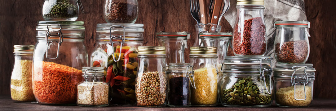 Food set. Raw cereals, pasta, groats, organic legumes and useful seeds in glass jars. Vegan source of protein and energy resources. Rustic wooden kitchen table background. Banner