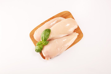 Raw chicken breasts and spices on wooden cutting board, close up
