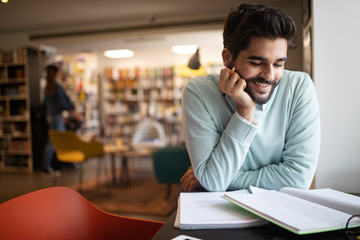 Happy student preparing exam and learning lessons in college library