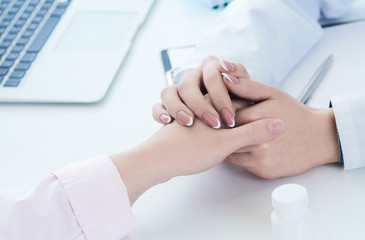 Friendly female doctor hands holding patient hand sitting at the desk for encouragement, empathy, cheering and support while medical examination. Just hands over the table.