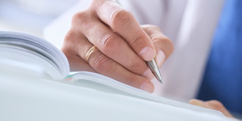 Male hand holding silver pen ready to make note in opened notebook sheet close-up. Businessman sign at work space make thoughts records at personal organizer white collar conference signature concept