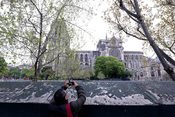 A man takes a picture of Notre-Dame Cathedral after a fire devastated large parts of the gothic gem in Paris