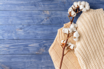 Cotton flowers with knitted sweaters on wooden background