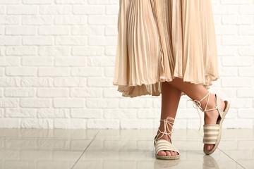 Obraz Stylish young woman in shoes near white brick wall - fototapety do salonu