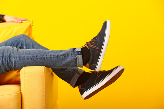 Stylish man in shoes sitting in armchair on color background