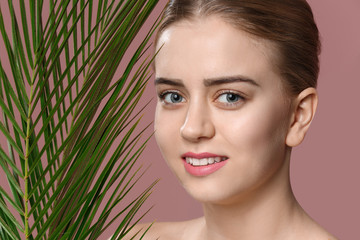 Beautiful young woman with laminated eyelashes and tropical leaves on color background