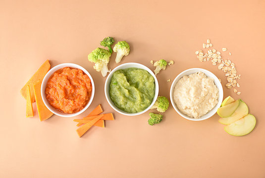 Bowls with healthy baby food on color background