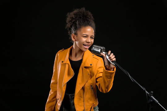 African-American girl with microphone singing against dark background