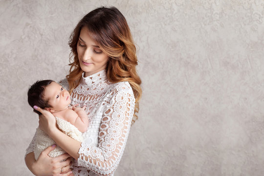 Pretty woman holding a newborn baby in her arms. Portrait of mother and little baby. Copy space