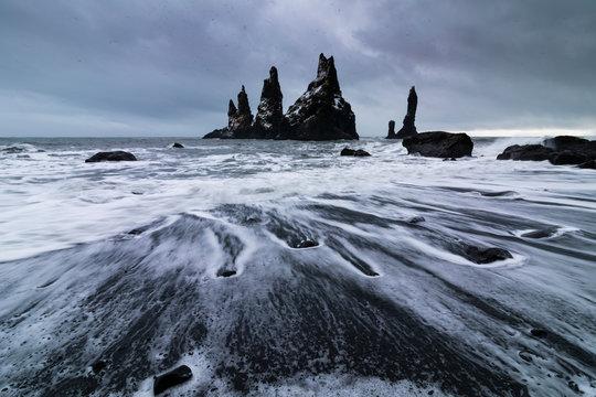 Basalt rocks Troll toes on black beach. at storm Reynisdrangar, Vik, Iceland.