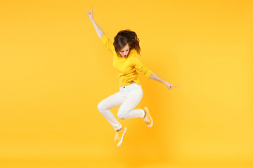 Cheerful funny young woman in summer casual clothes jumping and spreading hands isolated on yellow orange wall background in studio. People sincere emotions, lifestyle concept. Mock up copy space. Wall mural