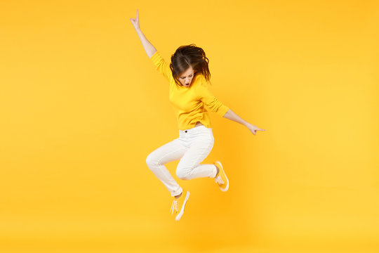 Cheerful funny young woman in summer casual clothes jumping and spreading hands isolated on yellow orange wall background in studio. People sincere emotions, lifestyle concept. Mock up copy space.