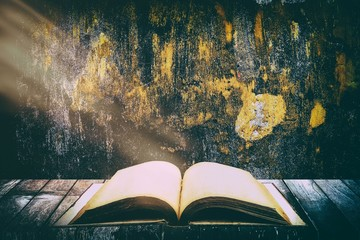 Old Vintage Holy Bible Opened on The Wooden Table with Grunge Concrete Wall Texture Background. Wall mural