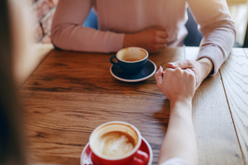 Young couple in love sitting in cafeteria and holding hands. On desk cups with coffee.