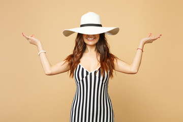 Smiling woman in black and white striped dress covering eyes with hat hold hands in yoga gesture, relaxing meditating isolated on pastel beige background. People sincere emotions, lifestyle concept.