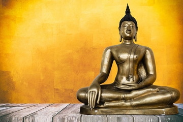 Ancient Buddha Image on Wooden Table with Gold Leaf Texture Background, Using Buddhist Religion Concept.