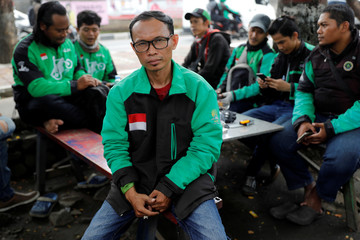 Suhandi, Grab motorcycle taxi driver who is running as a member of parliament from National Awakening Party (PKB) on the next election, sits as he poses for pictures in Jakarta