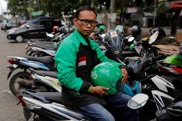 Suhandi, Grab motorcycle taxi driver who is running as a member of parliament from National Awakening Party (PKB) on the next election, poses for pictures in Jakarta