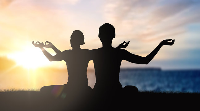 mindfulness, spirituality and outdoor yoga - silhouettes of couple meditating in lotus pose over sunset and sea background
