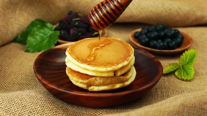Fototapete - Pour honey by a wooden dipper stick on a pile of pancake in a wooden bowl on sackcloth