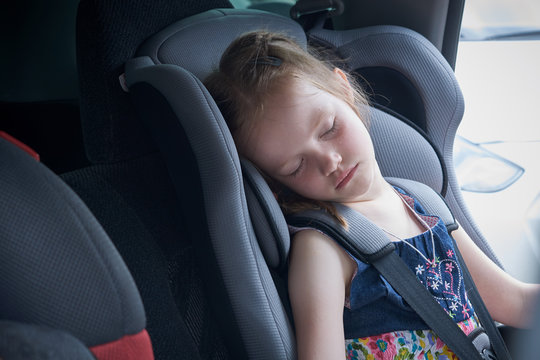 Little girl sleeps in a comfortable car seat for children. Soft and reliable car seat will save and save lives in a dangerous situation. The child put his head on the pillow of the chair and sleeping.