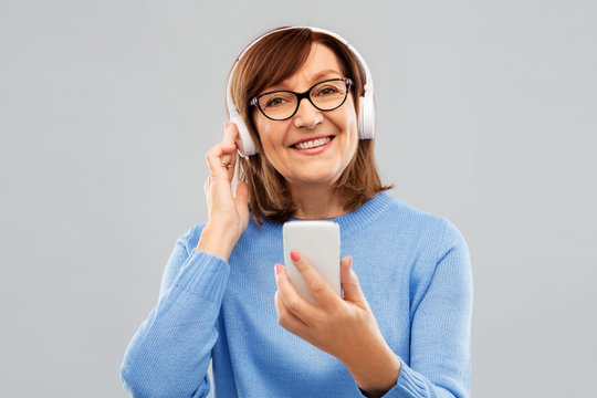 technology and old people concept - smiling senior woman in glasses and headphones listening music on smartphone over grey background