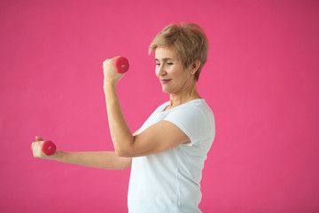 beautiful elderly woman in white t-shirt goes in for sports with dumbbells on a pink background