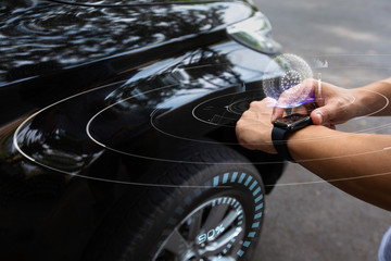 Man using smart watch check tire pressure to his smart car with wireless connecting, Future technology concept